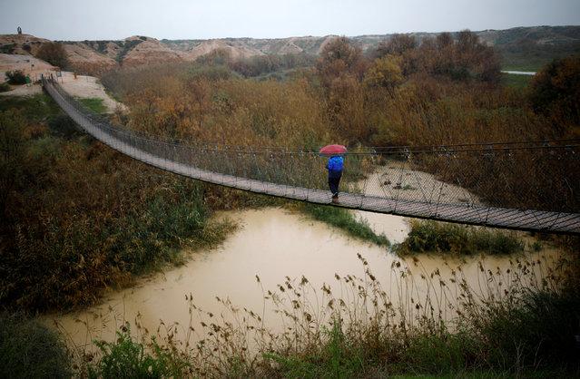 A man walks on a bridge crossing over the Besor stream on a rainy day, near Kibbutz Tze'elim in Israel's southern Negev desert February 16, 2017. (Photo by Amir Cohen/Reuters)