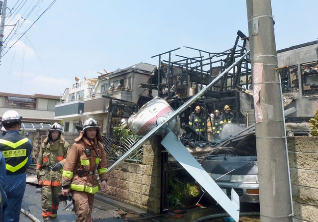 The tail section of a crashed light plane (C) and burning house are seen after the plane went down in a residential area and burst into flames, in Chofu, outskirt of Tokyo, in this photo taken by Kyodo July 26, 2015. A small airplane crashed into a residential area of the Japanese capital, Tokyo, on Sunday, setting fire to houses and cars and injuring at least two people, the Tokyo Fire Department said. (Photo by Reuters/Kyodo News)