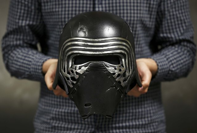 "A worker holds a replica of Kylo Ren's helmet from ""Star Wars: The Force Awakens"", in the Propshop headquarters at Pinewood Studios near London, Britain May 25, 2016. (Photo by Peter Nicholls/Reuters)"