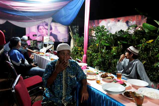Villagers watch films during a wedding party in Bogor, Indonesia, May 2, 2017. (Photo by Reuters/Beawiharta)