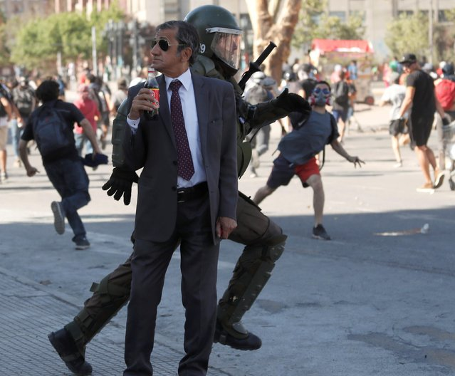 A man drinks a Frucola as a policeman chases demonstrators during a protest against Chile's government in Santiago, Chile on December 4, 2019. (Photo by Goran Tomasevic/Reuters)