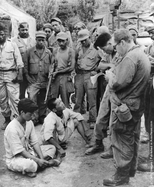 Suspected Communists captured near the lines are brought in for questioning, and later released during the Korean War