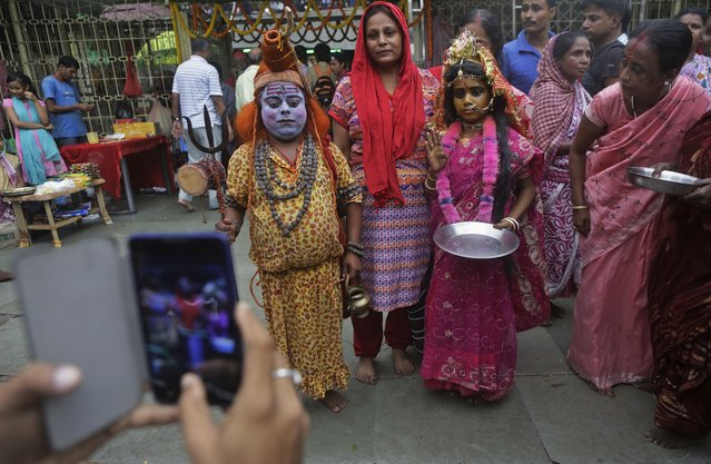 A devotee takes photographs on his mobile phone as his wife poses with a man dressed as Hindu god Shiva and a girl dressed like goddess Parvati during the Ambubasi festival at the Kamakhya Hindu temple in Gauhati, India, Sunday, June 22, 2014. The annual festival where hundreds of holy men from an esoteric form of Hinduism, gather to perform rituals at the temple begins on June 22. (Photo by Anupam Nath/AP Photo)