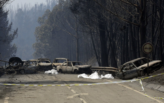 Burnt cars block the road between Castanheira de Pera and Figueiro dos Vinhos, central Portugal, Sunday, June 18 2017. (Photo by Armando Franca/AP Photo)