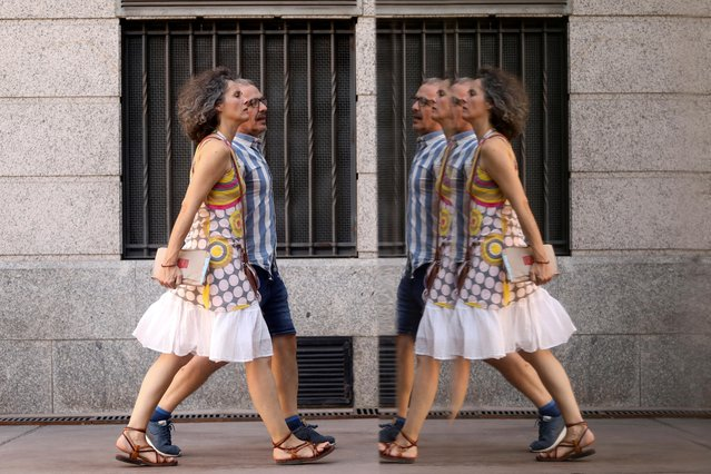 A couple are reflected in a glass wall as they walk beside CaixaForum cultural centre in Madrid, Spain, August 14, 2019. (Photo by Sergio Perez/Reuters)