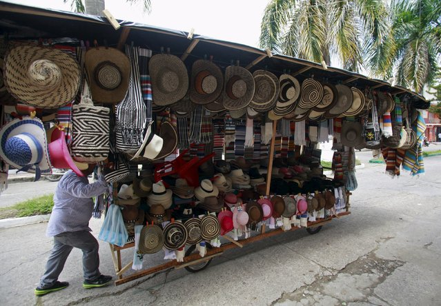 A seller pushes his home made cart with traditional hats during the 12th La Joropera festival in Acacias near Villavicencio in this October 14, 2012 file photo. Colombia is expected to release inflation numbers this week. (Photo by John Vizcaino/Reuters)