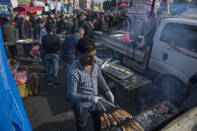 In this photo taken Thursday, December 12, 2019, a volunteer chef serves free meals of the popular barbecue of Kabab, to Iraqi protesters at the center of Baghdad, Iraq. (Photo by Nasser Nasser/AP Photo)