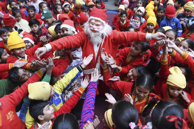 A girl dressed as Santa Claus distributes sweets to children during Christmas celebrations on Christmas Eve at a school in Amritsar on December 24, 2019. (Photo by Narinder Nanu/AFP Photo)