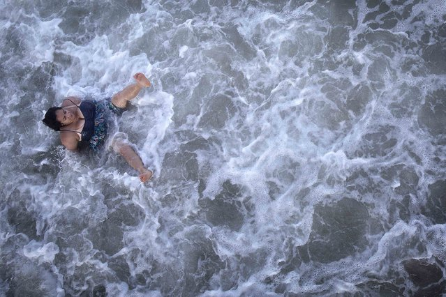 A woman gets knocked over in the surf on Coney Island in the Brooklyn borough of New York, July 2, 2014. Much of the east coast of the US is bracing for a for bad weather as a result of Hurricane Arthur. (Photo by Carlo Allegri/Reuters)