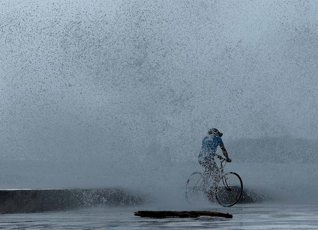 A man cycles along a dike in Legazpi city, Philippines, 03 December 2019. Typhoon Kammuri made landfall on 02 December and forced the closure of Ninoy Aquino International Airport in Manila. The typhoon also affected the ongoing Southeast Asian Games. According to the event organizers, several sporting events have been rescheduled or cancelled. (Photo by Zalrian Sayat/EPA/EFE)