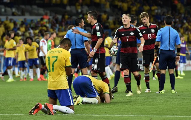 Brazil players sink to their knees after the World Cup semifinal soccer match between Brazil and Germany at the Mineirao Stadium in Belo Horizonte, Brazil, Tuesday, July 8, 2014. Germany won the match 7-1. (Photo by Martin Meissner/AP Photo)