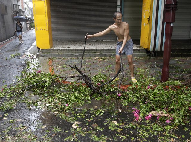 A man clears debris near his home in Taipei after Typhoon Soudelor hit Taiwan August 8, 2015. (Photo by Pichi Chuang/Reuters)