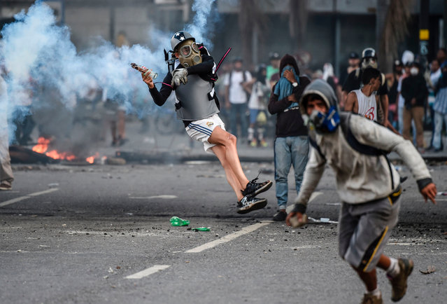 Venezuelan opposition demonstrators blocking the avenue during a protest against President Nicolas Maduro clash with riot police, in Caracas, on July 6, 2017. A political and economic crisis in the oil- producing country has spawned often violent demonstrations by protesters demanding Maduro' s resignation and new elections. The unrest has left 91 people dead since April 1. (Photo by Juan Barreto/AFP Photo)