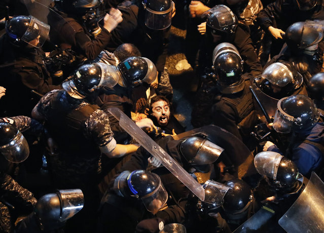 Riot police arrest an anti-government protester who was protesting outside a police headquarters demanding the release of those taken into custody the night before, outside a police headquarter, in Beirut, Lebanon, Wednesday, January 15, 2020. (Photo by Hussein Malla/AP Photo)