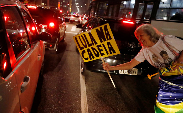 """A woman celebrates after former Brazilian President Luiz Inacio Lula da Silva, was convicted on corruption charges and sentenced to nearly 10 years in prison in Sao Paulo, Brazil July 12, 2017. The sign reads: """"Lula in Jail"""". (Photo by Nacho Doce/Reuters)"""