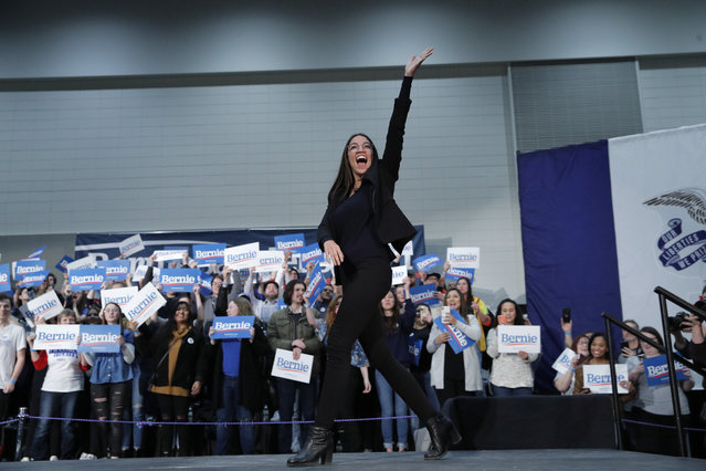 Rep. Alexandria Ocasio-Cortez, D-NY, waves as she walks on stage during a rally for democratic presidential candidate Sen. Bernie Sanders, I-Vt., Sunday, January 26, 2020, in Sioux City, Iowa. (Photo by John Locher/AP Photo)