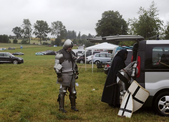 Men dressed as knights of the Teutonic Order prepare to participate in a reenactment of The Battle of Grunwald, in Grunwald July 12, 2014. (Photo by Filip Klimaszewski/Reuters)
