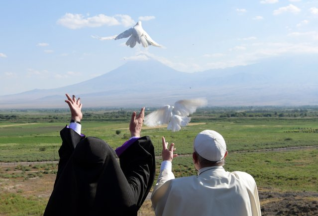 This handout picture taken on June 26, 2016 and released by the Vatican press office, Osservatore Romano, shows Pope Francis and Catholicos of All Armenians Karekin II releasing white doves in the direction of Mount Ararat during a visit to the Khor Virap monastery. (Photo by Osservatore Romano/AFP Photo)