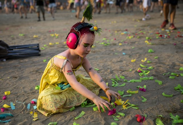 A girl plays with colourful papers at the 23rd Sziget (Island) Festival on Shipyard Island in Budapest, Hungary, 13 August 2015. (Photo by Balazs Mohai/EPA)