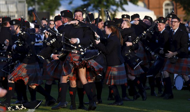 Members of the Shotts and Dykehead Pipe Band react to winning the annual World Pipe Band Championships at Glasgow Green, Scotland August 15, 2015. (Photo by Russell Cheyne/Reuters)