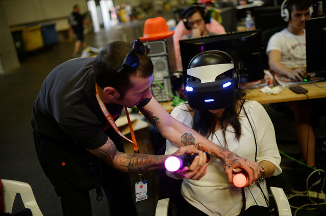A man gives instructions to a woman wearing a VR headset at the 25th Euskal Encounter, a four-day party during which over 5,000 computers are linked via local and high speed internet connections, in the Bilbao Exhibition Centre, Barakaldo, Spain, July 23, 2017. (Photo by Vincent West/Reuters)