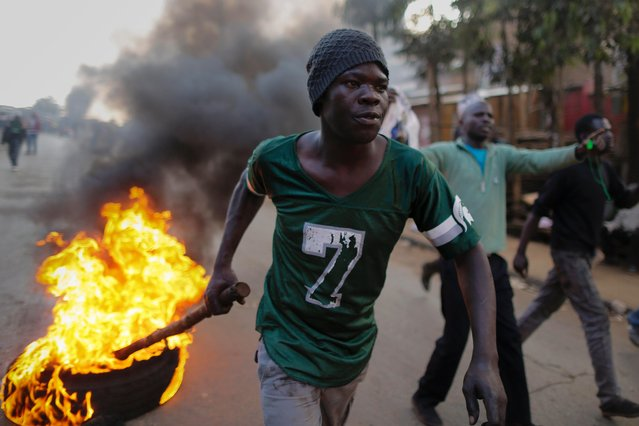 A supporter of the opposition leader Raila Odinga drags a burning tire down the street during a protest after Odinga announced that he rejects the provisional result of the presidential election announced by the electoral body, in Kibera slum, one of Odinga's strongholds in Nairobi, Kenya, 09 August 2017. (Photo by Dai Kurokawa/EPA)