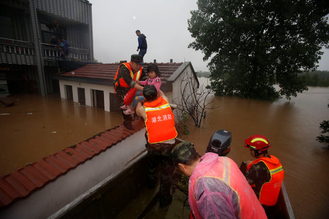 Rescuers save residents from a flooded area in Wuhan, Hubei Province, China, July 2, 2016. (Photo by Reuters/China Daily)