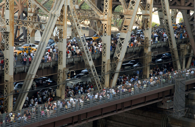 "Pedestrians and traffic leaving downtown Manhattan crossing the Queensboro Bridge after the onset of the largest power blackout in American history, August 14, 2003. The Northeast blackout of 2003 was a widespread power outage that occurred throughout parts of the Northeastern and Midwestern United States and the Canadian province of Ontario on Thursday, August 14, 2003, just after 4:10 p.m. EDT. Some power was restored by 11 p.m. Many others did not get their power back until two days later. In more remote areas it took nearly a week to restore power. At the time, it was the world's second most widespread blackout in history, after the 1999 Southern Brazil blackout. The outage, which was much more widespread than the Northeast Blackout of 1965, affected an estimated 10 million people in Ontario and 45 million people in eight U.S. states. The blackout's primary cause was a programming error or ""bug"" in the alarm system at a FirstEnergy Corporation control room in Ohio. The lack of an alarm left operators unaware of the need to re-distribute power after overloaded transmission lines hit unpruned foliage, triggering a ""race condition"" in the energy management system software, a bug affecting the order of operations in the system. What would have been a manageable local blackout cascaded into massive widespread distress on the electric grid. (Photo by Robin Platzer/FilmMagic)"