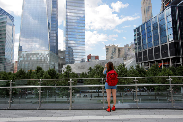 A woman takes a photo from the newly opened Liberty Park above Liberty Street on the World Trade Center site in the Manhattan borough of New York, U.S., June 29, 2016. (Photo by Andrew Kelly/Reuters)