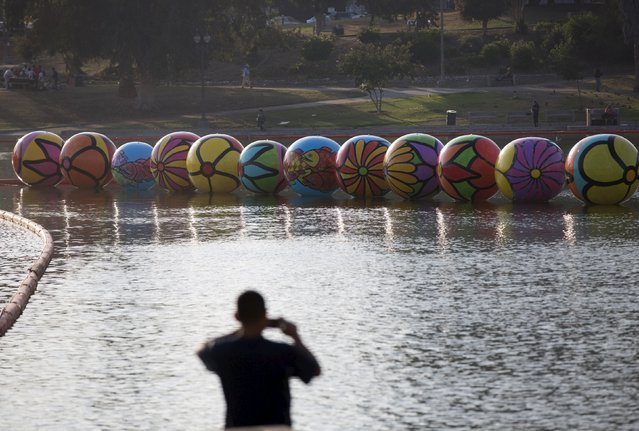 "A person takes a photo of inflated spheres in MacArthur Park Lake during the installation of Portraits of Hope's exhibition ""Spheres at MacArthur Park"" in Los Angeles, California August 21, 2015. (Photo by Mario Anzuoni/Reuters)"