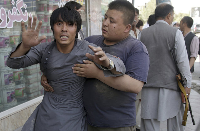 A shocked man shouts slogans against the Afghan President after he ran out of the Shiite mosque during an ongoing attack, Kabul, Afghanistan, Friday, August 25, 2017. Gunmen stormed a Shiite mosque in the Afghan capital while worshippers were at Friday prayers, setting off an explosion that killed a security guard outside and pushing into the shrine, officials said. (Photo by Massoud Hossaini/AP Photo)