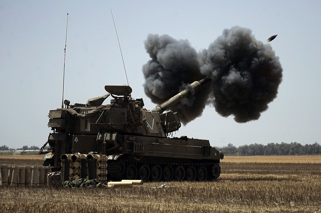 """An Israeli artillery fires a 155mm shell towards targets in the Gaza Strip from their position near Israel's border with the Palestinian enclave on August 2, 2014. The Israeli army informed residents of Beit Lahiya in northern Gaza that it was """"safe"""" to return to their homes, as witnesses said troops were seen withdrawing from the area. (Photo by David Buimovitch/AFP Photo)"""