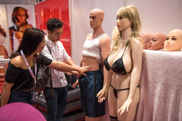Visitors touche an adult s*x toy doll at a stall during the Asia Adult Expo in Hong Kong on August 30, 2017. (Photo by Jayne Russell/The Sun)
