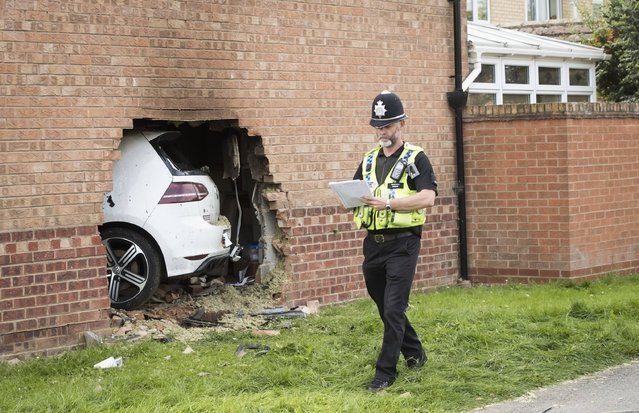 A police officer walks past the scene in Clifton, York, England after a Volkswagen Golf car left the road and hit a house where a man inside the property suffered serious injuries, although they are not believed to be life threatening, Sunday September 3, 2017. A man in his twenties, believed to be the driver of the car, has been arrested in connection with the incident. (Photo by Danny Lawson/PA Wire via AP Photo)