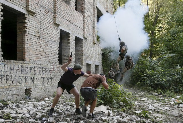 A mock terrorist detains a hostage as members of the Ukrainian Interior Ministry's special battalion Kiev-1 rappel down a building during an anti-terror drill in Kiev, Ukraine, August 28, 2015. (Photo by Valentyn Ogirenko/Reuters)