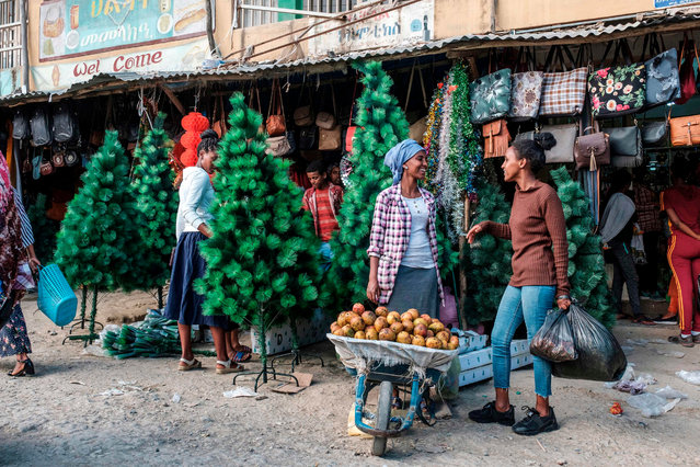 A woman sells mangoes in front of a shop selling Christmas trees and decoration at the market in Mekelle on January 4, 2020. The Ethiopian Orthodox Christmas is celebrated each year on January 7 and it's not usual to include western Christmas decoration, but according to local traders this started to change in Mekelle around 5 years ago. (Photo by Eduardo Soteras/AFP Photo)