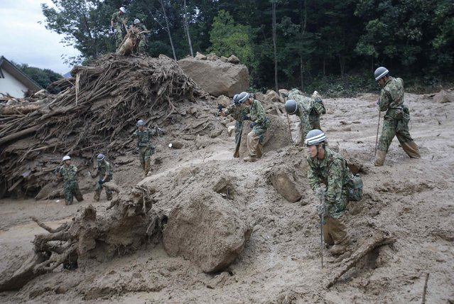 Japan Self-Defense Force soldiers search for survivors at the site of a landslide at Asaminami ward in Hiroshima, August 20, 2014. At least 36 people, including several children, were killed in Japan on Wednesday, when landslides triggered by torrential rain slammed into the outskirts of the western city of Hiroshima, and the toll could rise further, police said. (Photo by Toru Hanai/Reuters)