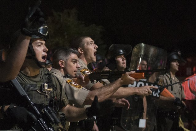 Security forces charge demonstrators after being hit by water bottles during a protest against the shooting of unarmed black teen Michael Brown in Ferguson, Missouri August 20, 2014. Police in riot gear ordered dozens of lingering demonstrators in Ferguson, Missouri, to disperse late on Tuesday and charged into the crowd to make arrests as relative calm dissolved amid protests over the police shooting death of Brown in the St. Louis suburb. (Photo by Adrees Latif/Reuters)