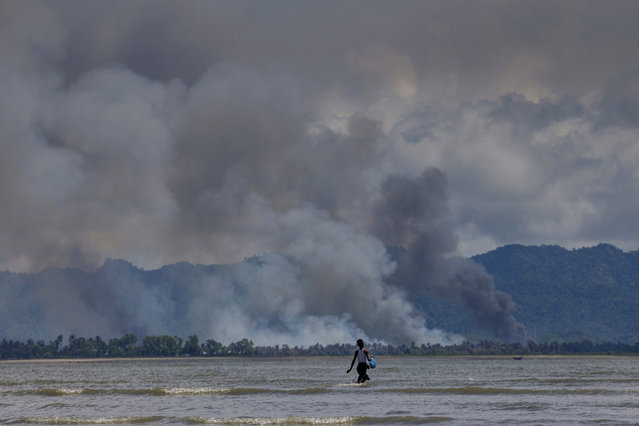 A Bangladeshi boy walks towards a parked boat as smoke rises from across the border in Myanmar, at Shah Porir Dwip, Bangladesh, Thursday, September 14, 2017. Nearly three weeks into a mass exodus of Rohingya fleeing violence in Myanmar, thousands were still flooding across the border Thursday in search of help and safety in teeming refugee settlements in Bangladesh. Those who arrived Wednesday in wooden boats described ongoing violence in Buddhist-majority Myanmar, where smoke could be seen billowing from a burning village, suggesting more Rohingya homes had been set alight. (Photo by Dar Yasin/AP Photo)