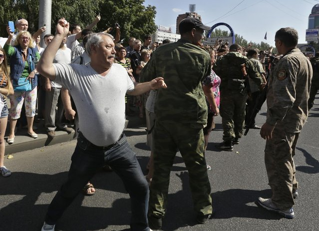 A man throws an egg at captured Ukrainian army prisoners as they're escorted by Pro-Russian rebels in a central square in Donetsk, eastern Ukraine, Sunday, August 24, 2014. (Photo by Sergei Grits/AP Photo)