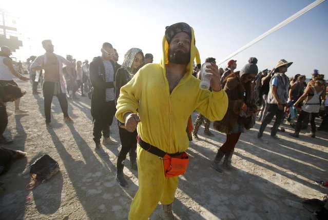 """Dan Drahos dances at the Robot Heart during the morning hours at the Burning Man 2015 """"Carnival of Mirrors"""" arts and music festival in the Black Rock Desert of Nevada, August 31, 2015. (Photo by Jim Urquhart/Reuters)"""