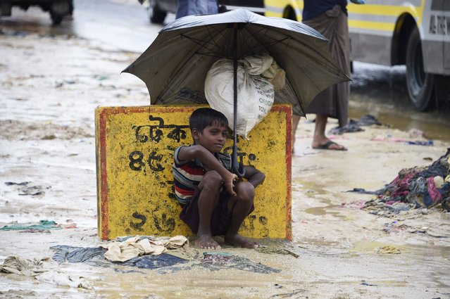 """A young Rohingya refugee shelters from the rain with an umbrella while sitting at Kutupalong refugee camp in the Bangladeshi locality of Ukhia on September 19, 2017. Pressure grew on Myanmar on September 18 as a rights group urged world leaders to impose sanctions on its military, which is accused of driving out more than 410,000 Rohingya Muslims in an orchestrated """"ethnic cleansing"""" campaign. (Photo by Dominique Faget/AFP Photo)"""