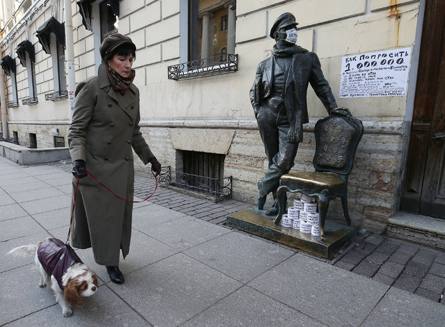 A woman walking a dog by a statue of Ostap Bender, a character of satirical novels by the Soviet authors Ilf and Petrov in St Petersburg, Russia on March 27, 2020. (Photo by Peter Kovalev/TASS)