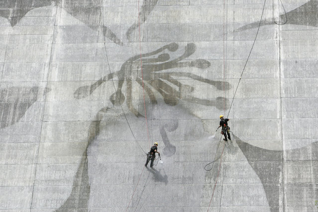 Two men clean the Matsudagawa Dam in Japan. (Photo by Caters News Agency)