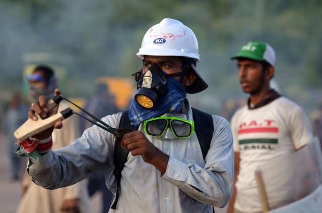 A Pakistani supporter of cleric Tahirul Qadri uses a slingshot to lob a stone toward riot police during a protest in Islamabad, on September 1, 2014. (Photo by Aamir Qureshi/AFP Photo)