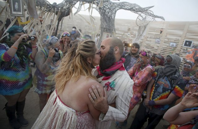 "Shandi Trolson (L) and Jordan Lenaburg kiss as they are married during a wedding ceremony at the Burning Man 2015 ""Carnival of Mirrors"" arts and music festival in the Black Rock Desert of Nevada, September 2, 2015. (Photo by Jim Urquhart/Reuters)"