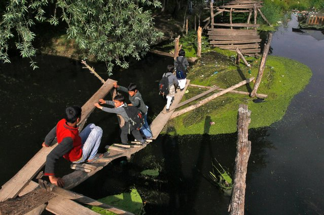 Kashmiri children cross a damaged footbridge built over a stream, on their way back home from school in Srinagar in this May 11, 2012, file photo. (Photo by Danish Ishmail/Reuters)
