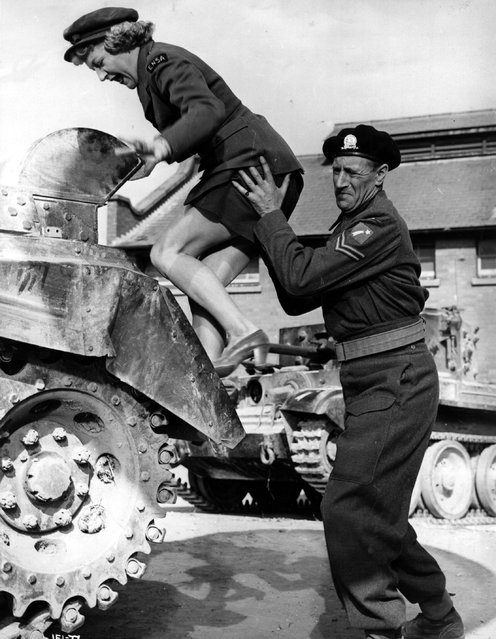 """Arthur Howard, the British character actor demonstrates the intricacies of tank mechanism to Dora Bryan, the stage and film comedienne in a scene from the film """"The Intruder"""", directed by Guy Hamilton for British Lion, 1954. (Photo by Hulton Archive)"""