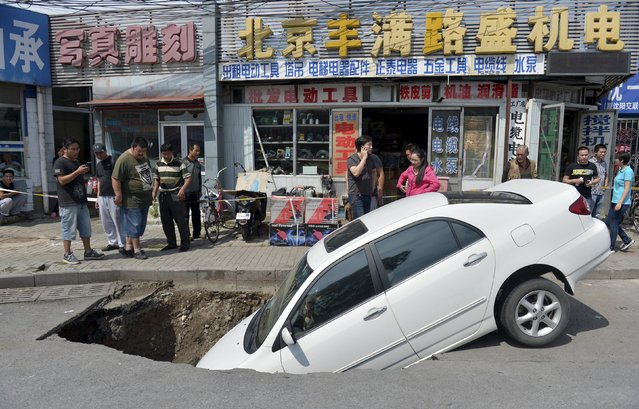 Bystanders look at a car that has partially fallen into a small sinkhole along a street in Beijing, China, September 6, 2015. According to local media, no one was injured during the incident. (Photo by Reuters/Stringer)