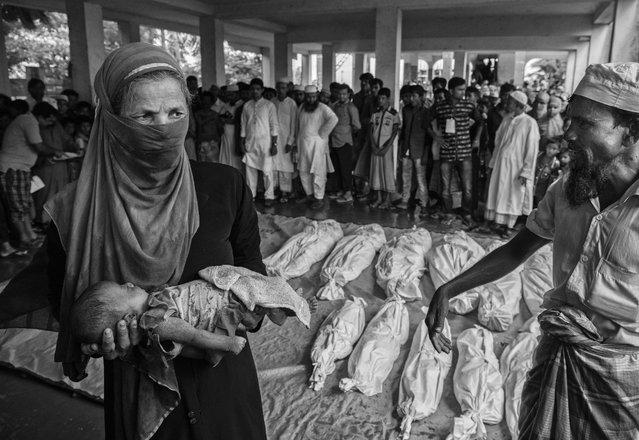 A woman carries the body of a Rohingya refugee boy as others are seen wrapped in white sheets prior to burial  after they died when their boat capsized while fleeing Myanmar  on September 29, 2017 in Cox's Bazar, Bangladesh. (Photo by Kevin Frayer/Getty Images)